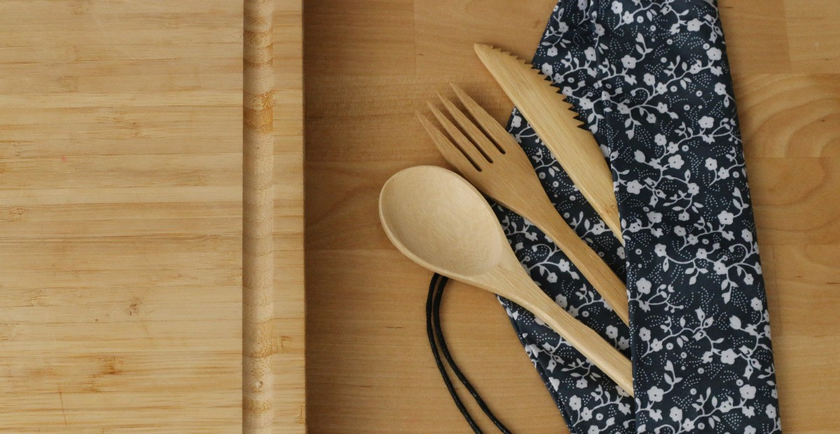 Wooden Utensils on wooden board in a black carrying case are an example of sustainable home goods