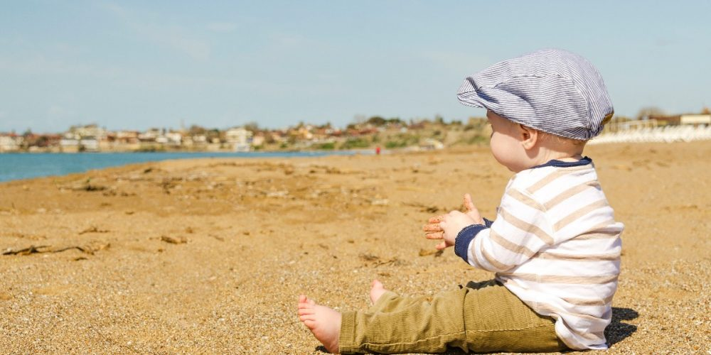 This baby is sitting ona beach wearing a brand that supports ethical kids clothes